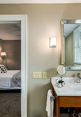 Interior view from the en suite bathroom of Room Four into the bedroom showing crisp, white linens