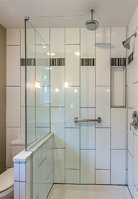 Looking into the glass walled shower, with rainfall showerhead and grab bar