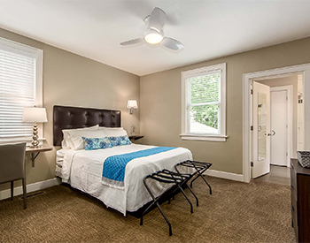 Looking into Room Two with view of desk, bathroom, and bed made with white linens and blue accent pillows