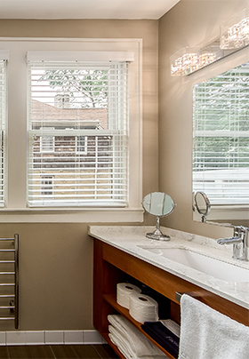 of bathroom showing open shelf teak vanity and white linens
