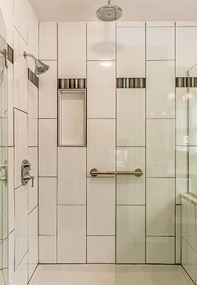 Walk-in shower in Room Three showing glass walls and white subway tiles with gray accent tiles