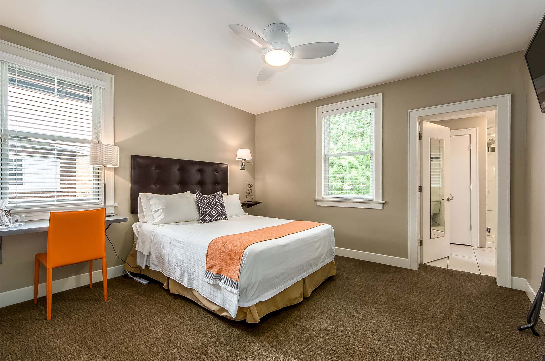 Looking into Room Five with view of desk, and bed made with white linens and orange accents