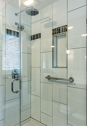 A well lit glass shower with multiple showerheads.