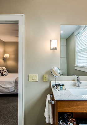 Interior view from the en suite bathroom of Room One into the bedroom showing crisp, white linens