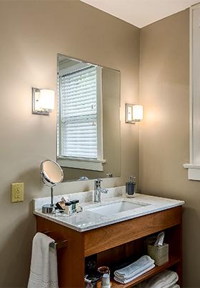 Open shelf hardwood bathroom vanity with pale gray, quartz countertop in Room One