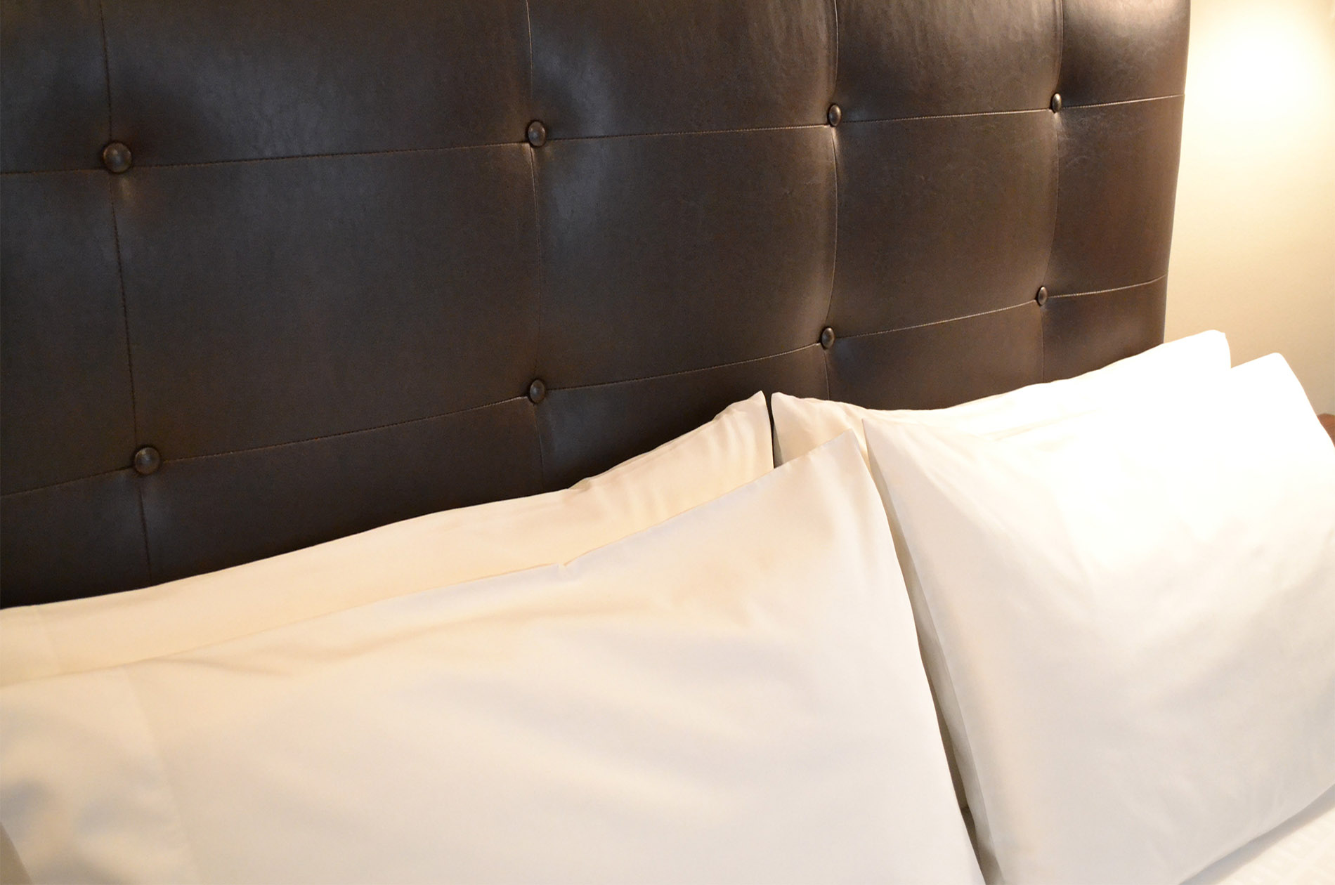 Dark brown headboard of bed contrasted with fluffy white pillows.