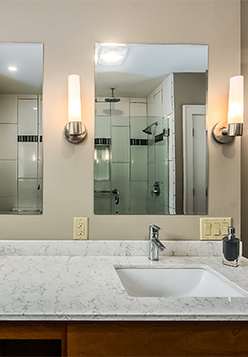 Bathroom counter with multiple mirrors and sink. In mirror, glass shower with multiple showerheads visible.
