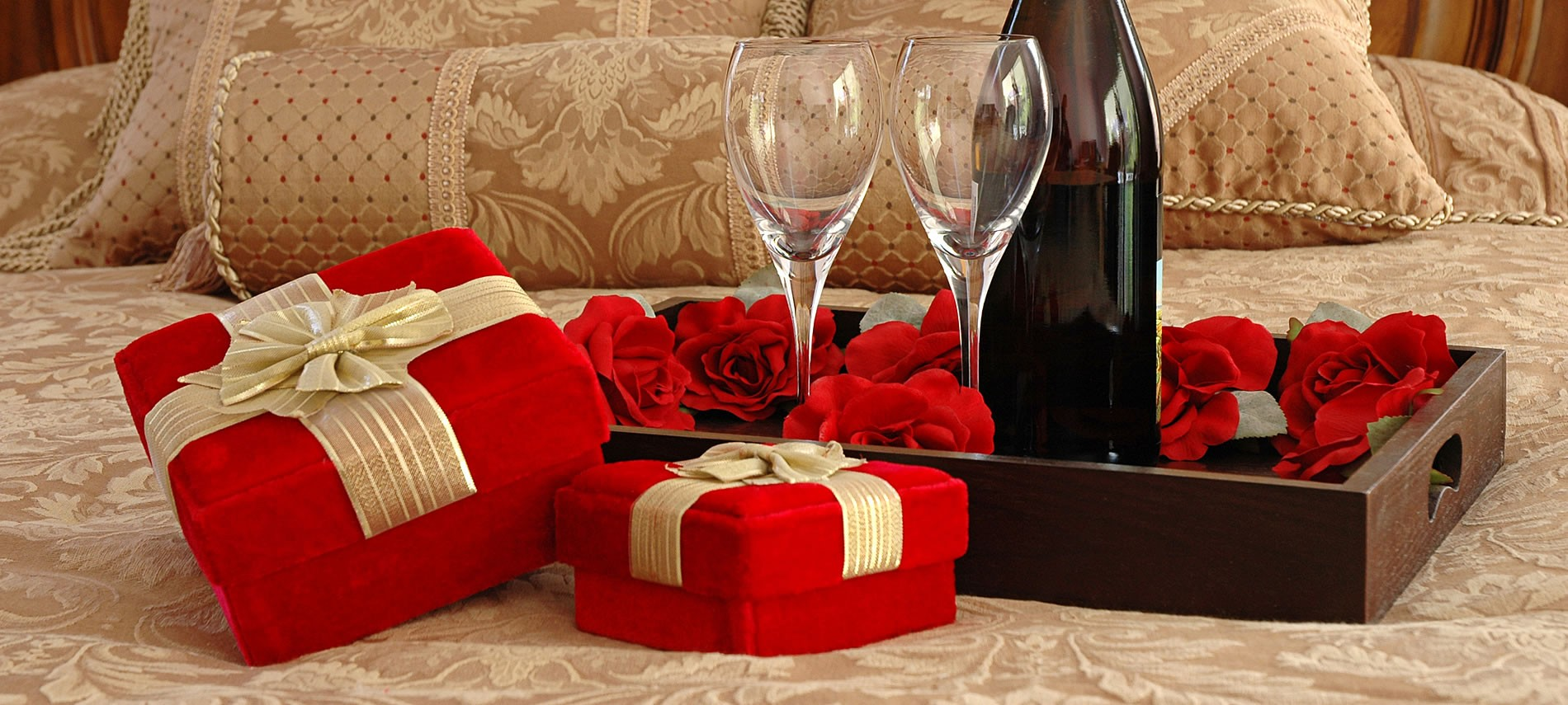 Red velvet boxes with decorative bows next to a dark wooded bed tray with wine, wine glasses and red roses, all set upon a tan bed.