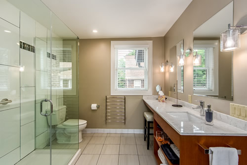 Long view into bathroom showcasing modern appointments. Lamps upon the wall above sink, and glass shower opposite.